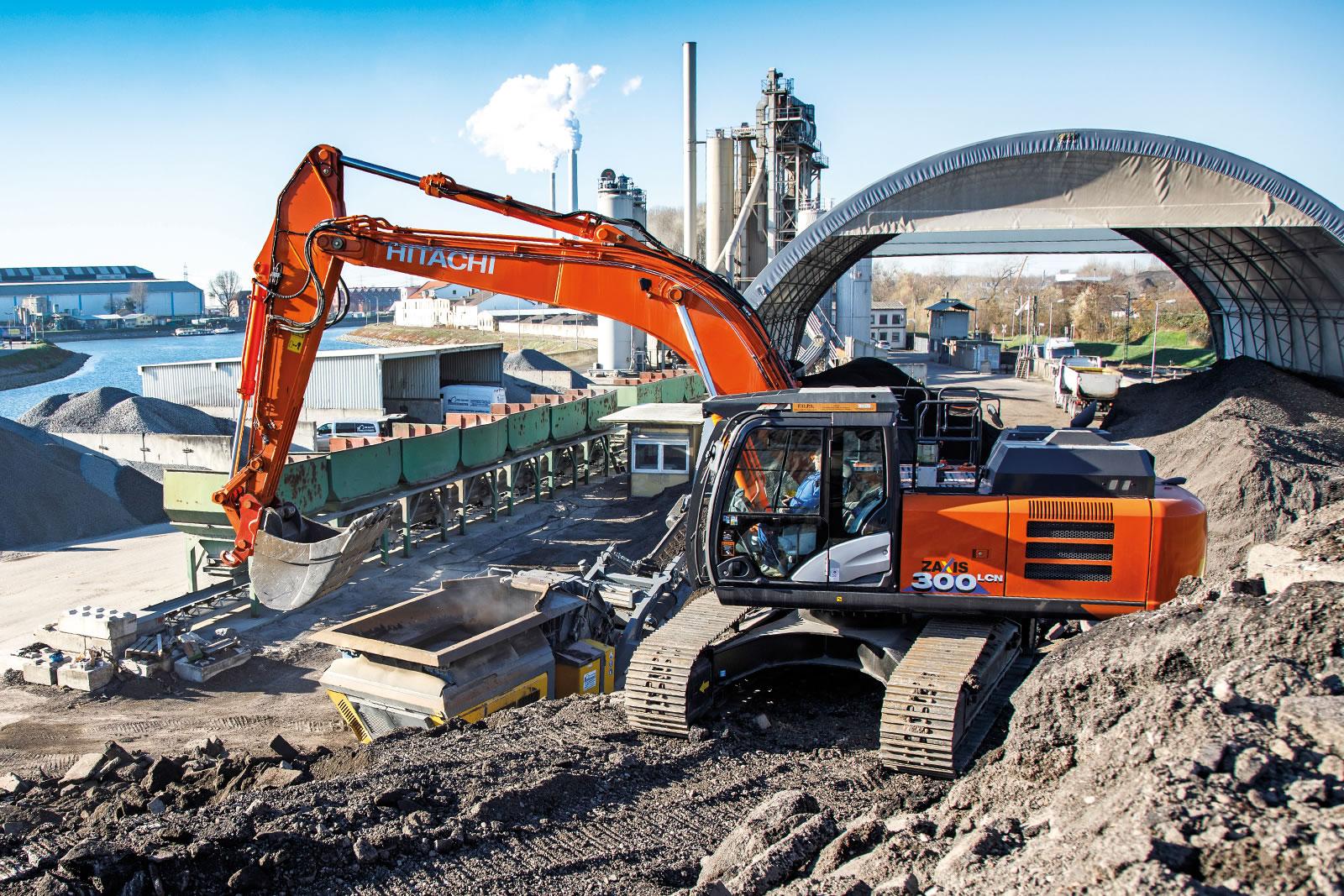 Hitachi ZX300LCN-6 excavator loads asphalt on to a mobile crusher