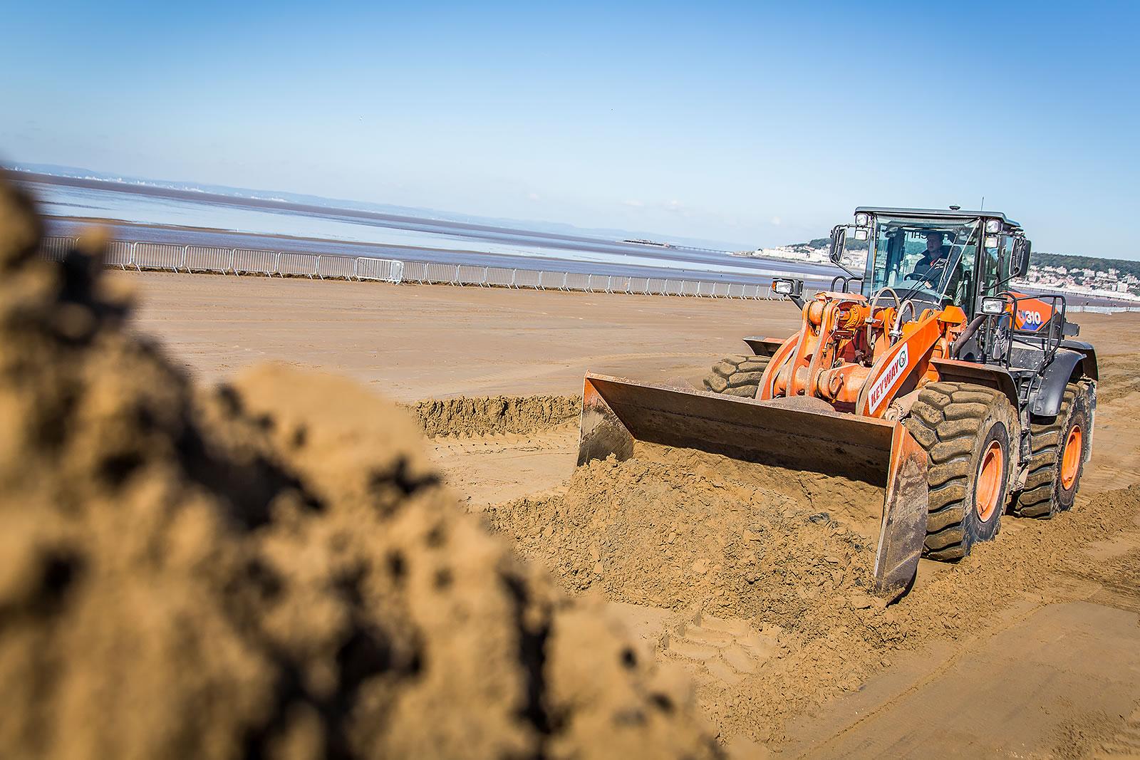 Hitachi ZW310-6 wheel loader moves sand on Weston beach
