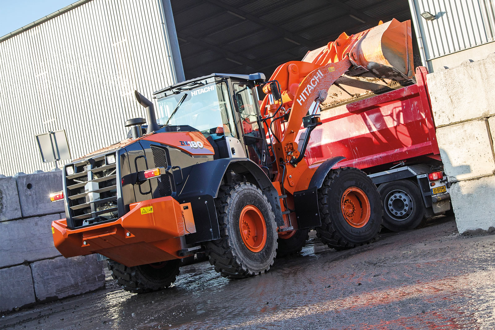 Hitachi ZW180-6 wheel loader loading material into a truck
