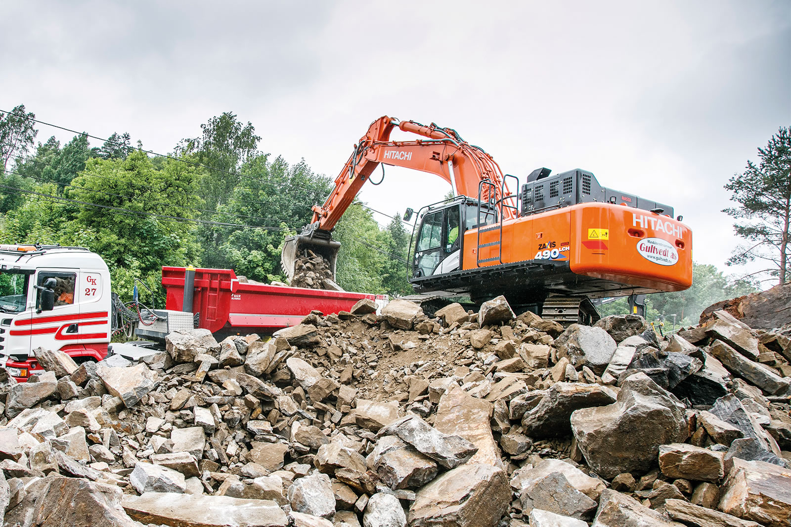 Hitachi ZX490LCH-6 excavator breaks up rock