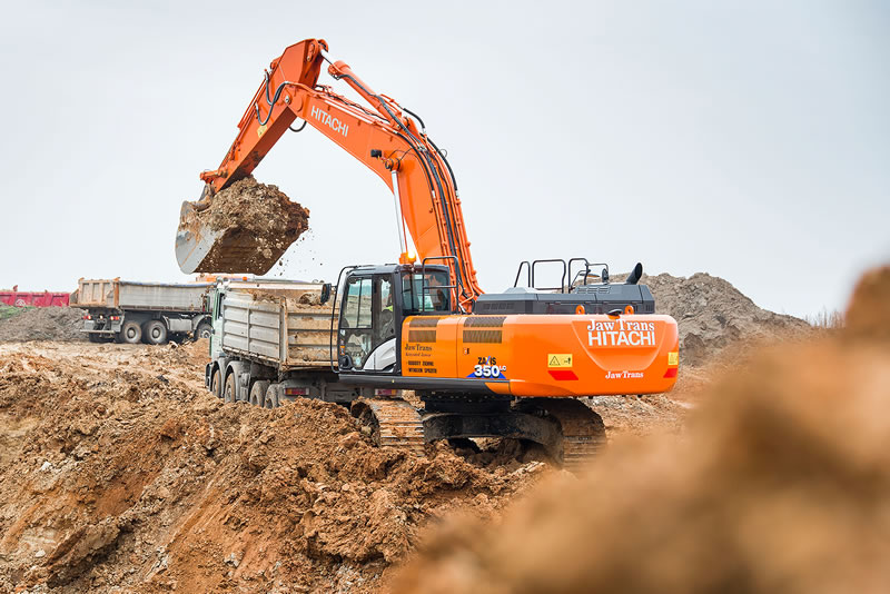 Hitachi ZX350LC-6 excavator empties earth onto a truck for the road